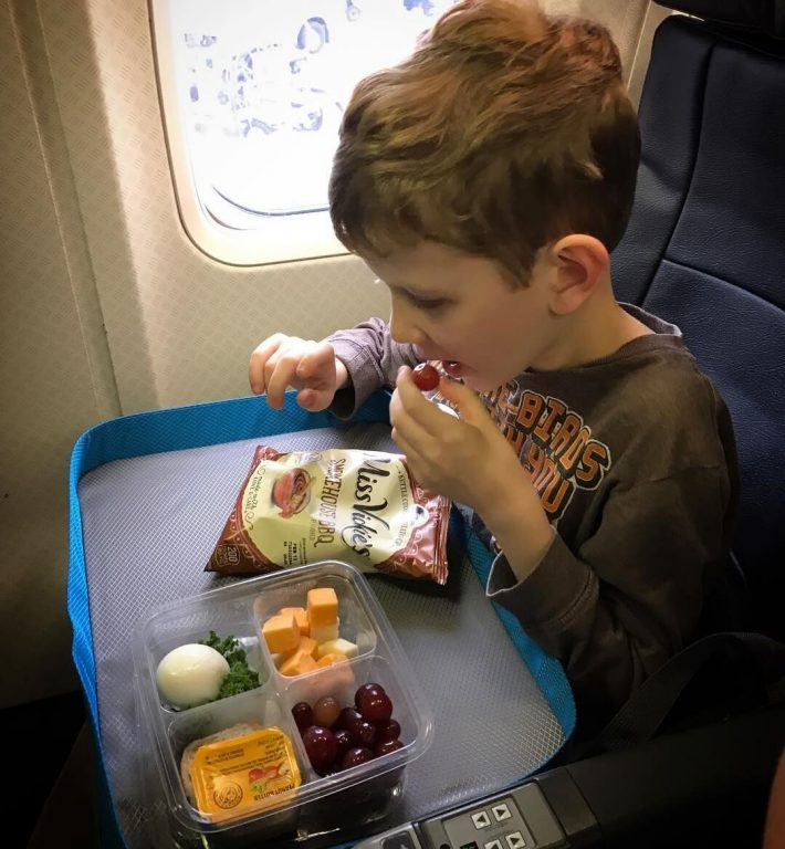 A picture of a boy having some snacks on an airplane