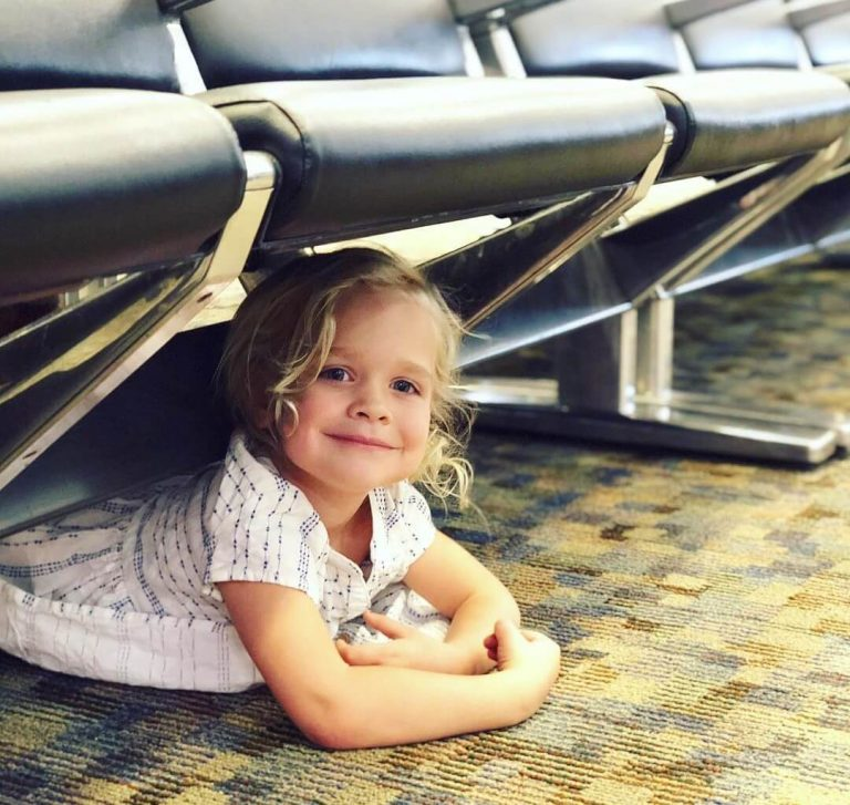 A picture of a young girl under chairs in an airport lounge