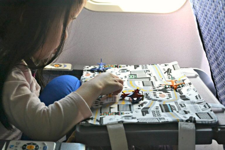 A picture of a child playing on an airplane tray table