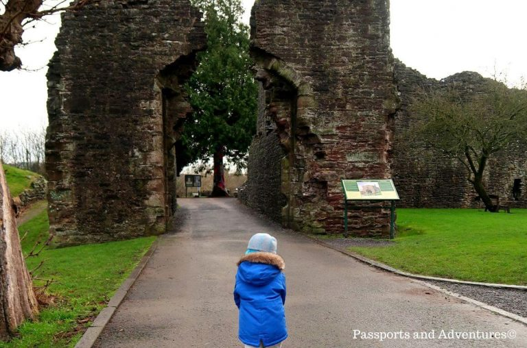 A little boy in a blue hat and coat making his way through the ruined gates of Abergavenny Castle in Wales.