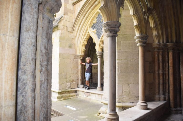 A young boy standing in an archway in the castle in Norwich