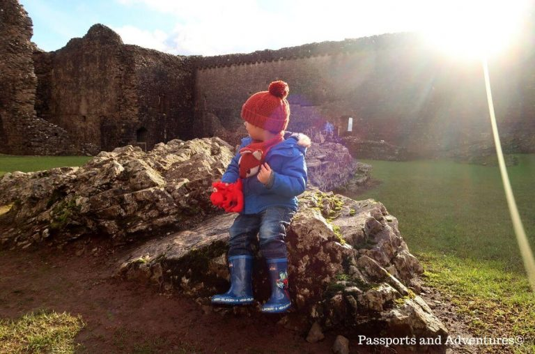 A little boy in jeans, blue wellies, a blue coat and orange hat sitting on a mound of rocks with a red dragon teddy in his hand.