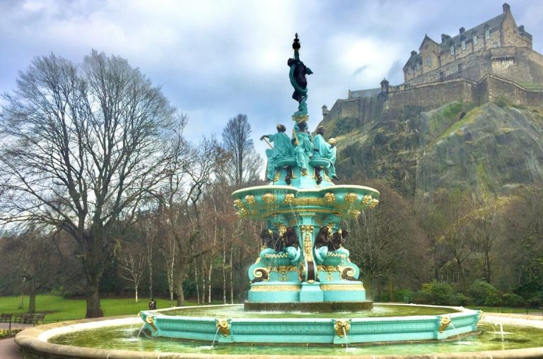 A picture of a fountain in the gardens below Edinburgh Castle with the castle on its hilltop in the background