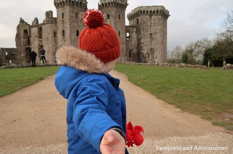 A little boy standing in front of Raglan Castle in a blue coat, red hat and with a red dragon teddy bear in his hand