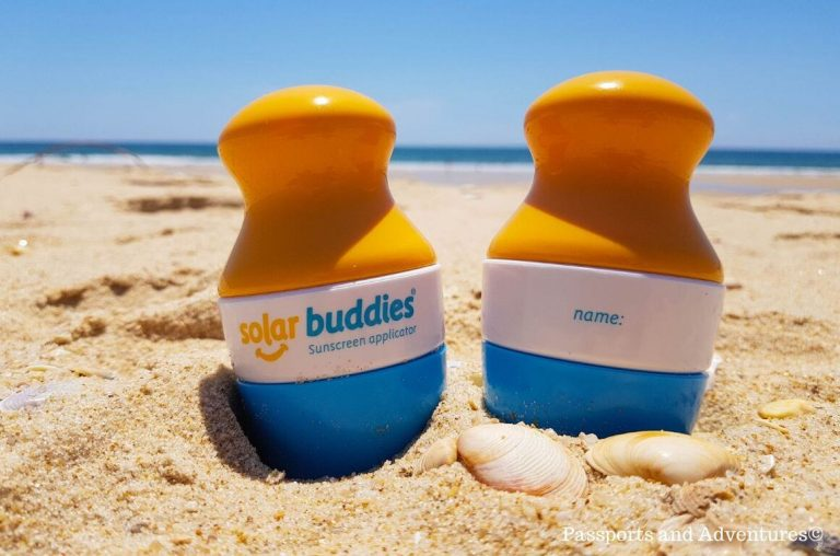A picture of two Solar Buddies Applicators on a sandy beach with the sea in the background