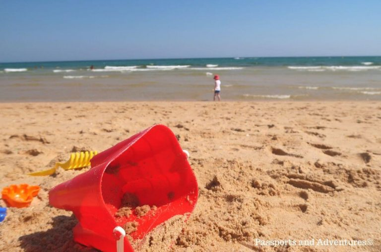 A close up picture of a sand castle bucket and spade with a young boy at the waters edge in the background