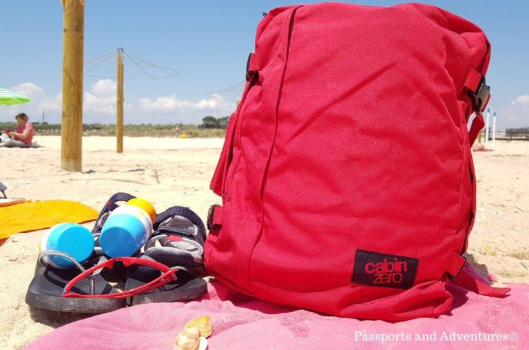 A picture of a red Cabin Zero bag on a beach towel with flip flops, sunglasses and sun cream beside it