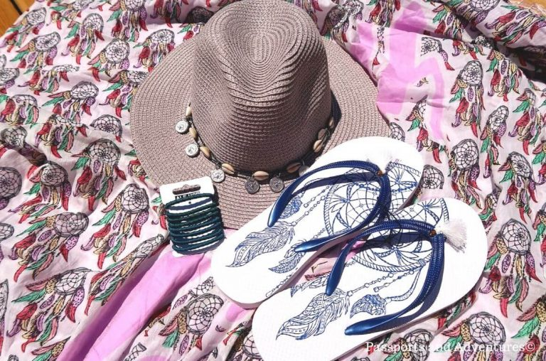 A flat lay picture of a beach sarong with a hat, flip flops and hair bands on it