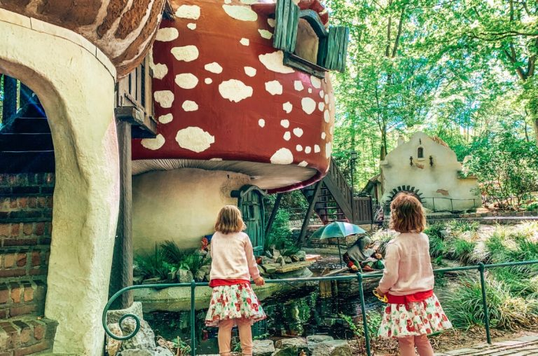 Two twin girls in front of a mushroom house in Efteling, the Netherlands