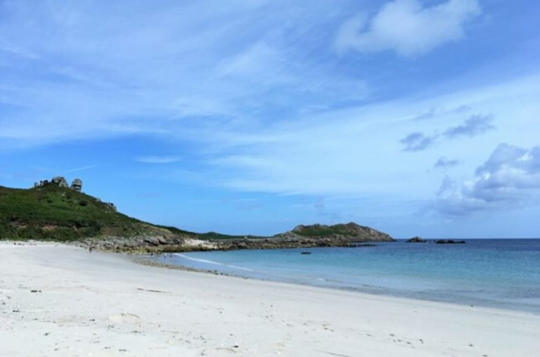 A beautiful sandy beach with blue skies in the Isles of Scilly