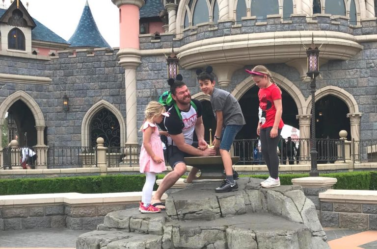 A picture of a dad and son trying to get the Sword in the Stone at Disneyland Paris