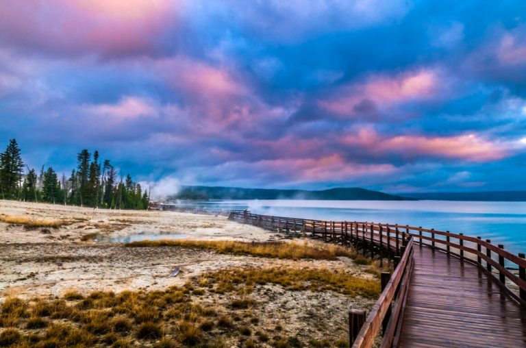 A picture of a pink and blue sky over the boardwalks at the West Thumb Geyser Basin in Yellowstone