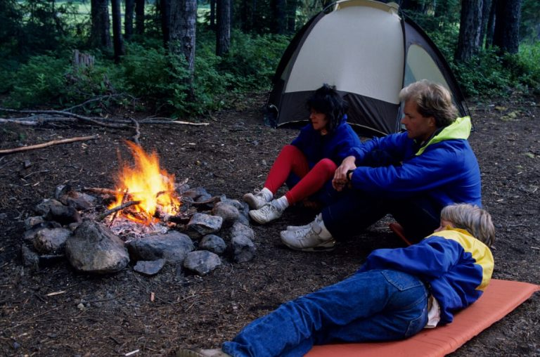 A picture of a Dad and two kids sat around a campfire with a tent in the background