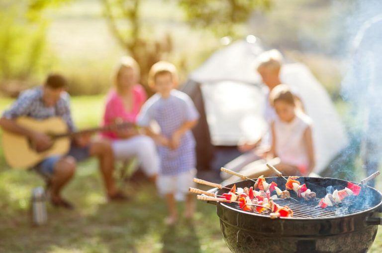 A picture with a BBQ in focus in the bottom right hand corner, with kebab skewers cooking and a family and tent blurred in the background