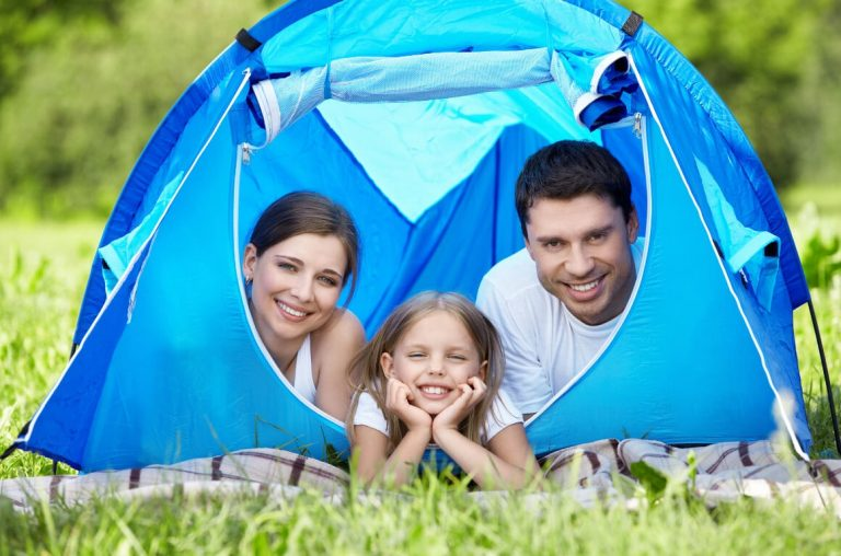 A family of three looking out from a blue tent in a green field of grass