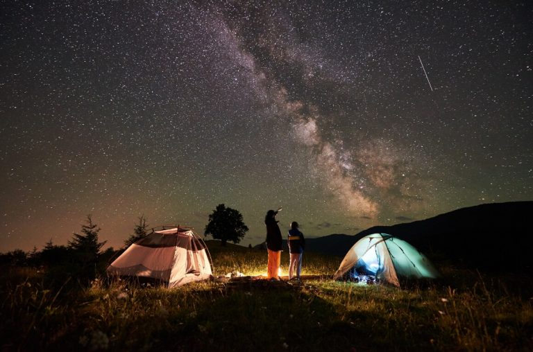 A picture at night of two tents with two people looking up at the Milky Way in the sky with a shooting star