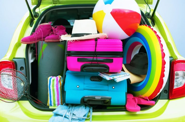 A car boot full of suitcases, beach balls, inflatable ring and other holiday items