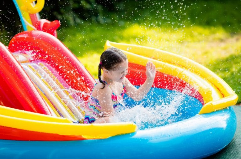 A young girl splashing water in an inflatable pool with a slide behind her