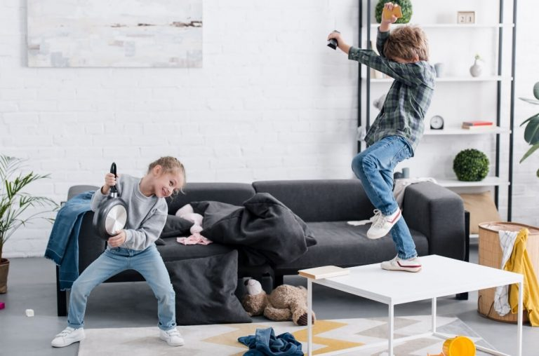 Two kids dancing and rocking in a living room