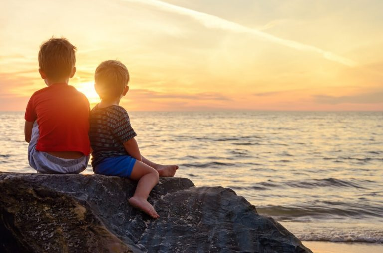 Two young boys sitting on a rock at the seashore watching the sun setting