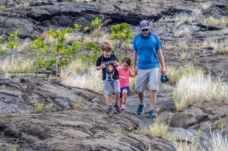 A Dad anf two kids walking on rocky ground through the Hawaii Big Island National Park