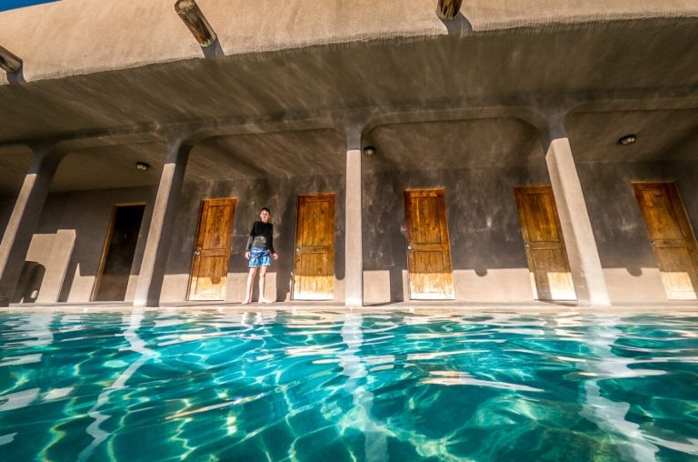 A picture of a boy in swimming trunks standing in front one of the blue spring pools at Miracle Hot Springs