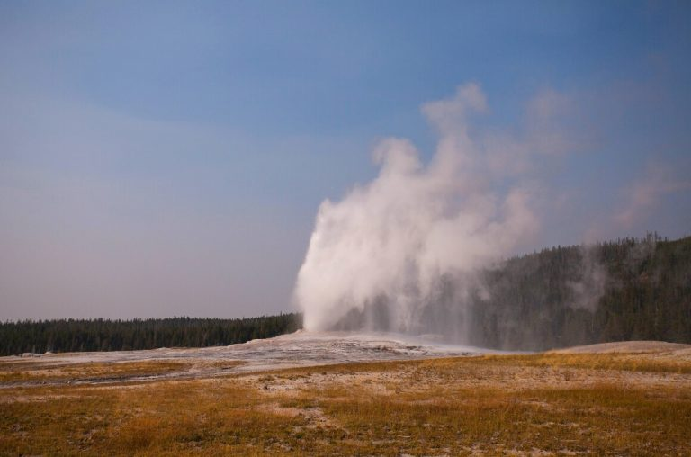 A picture of Old Faithful Geyser, Yellowstone National Park erupting with water shooting into the air
