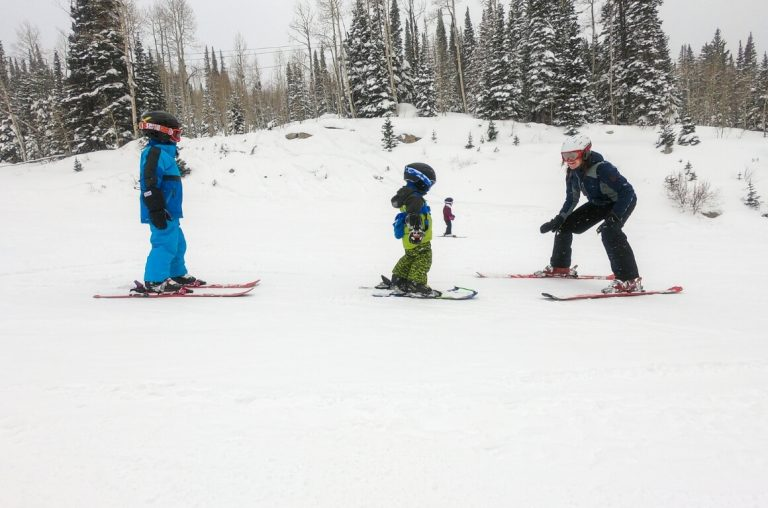 A picture of three kids in ski-wear and on skis in the snow with snow-covered trees in the background at Park City in Utah