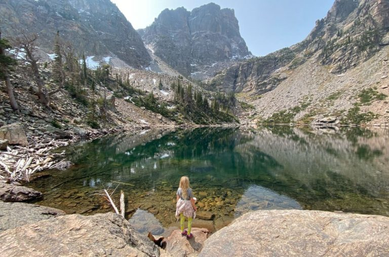 A girl standing at the edge of a lake in the foreground with the rocky mountains on the Rocky Mountains National Park in the background