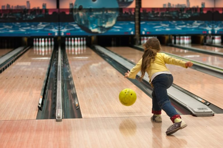 A picture of a young girl bowling in a bowling alley