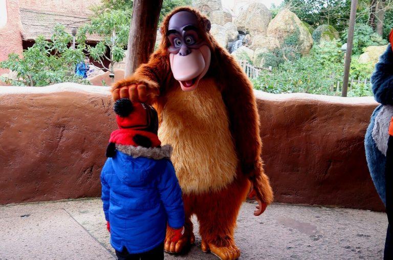 A little boy in a blue coat meeting King Louis at Disneyland Paris