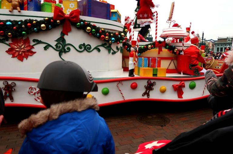 A little boy in a blue coat watching a Christmas parade at Disneyland Paris