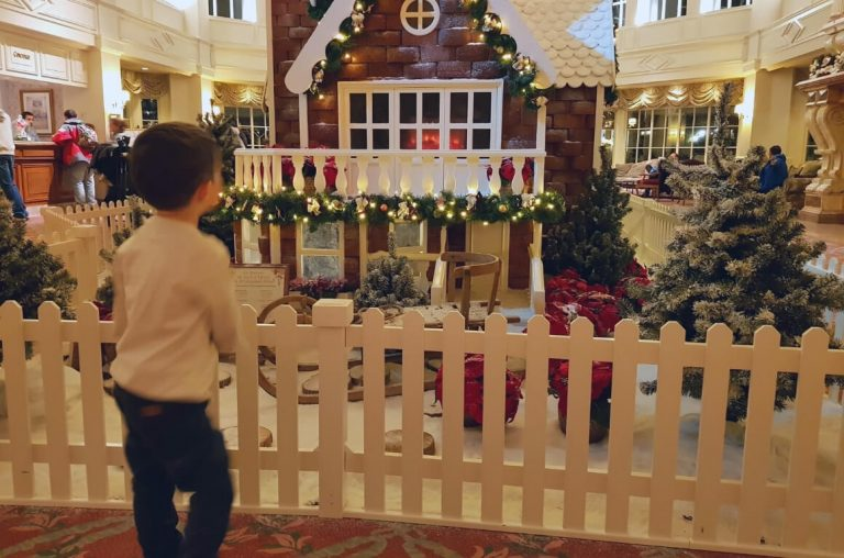 A little boy in front of the gingerbread house in the lobby of the Disneyland Paris Hotel