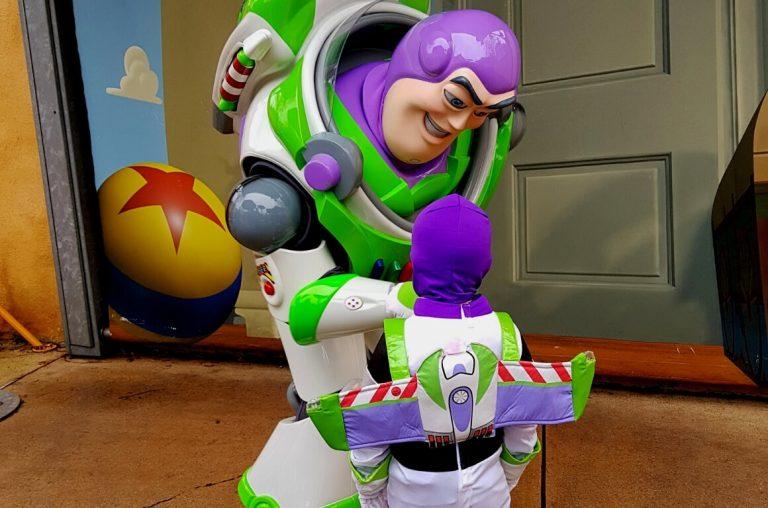 A little boy in a Buzz Lightyear costume meeting the character Buzz Lightyear in Disneyland Paris