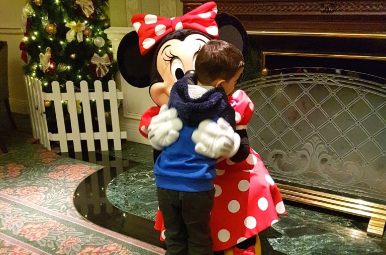 A little boy in a blue jumper meeting Minnie Mouse