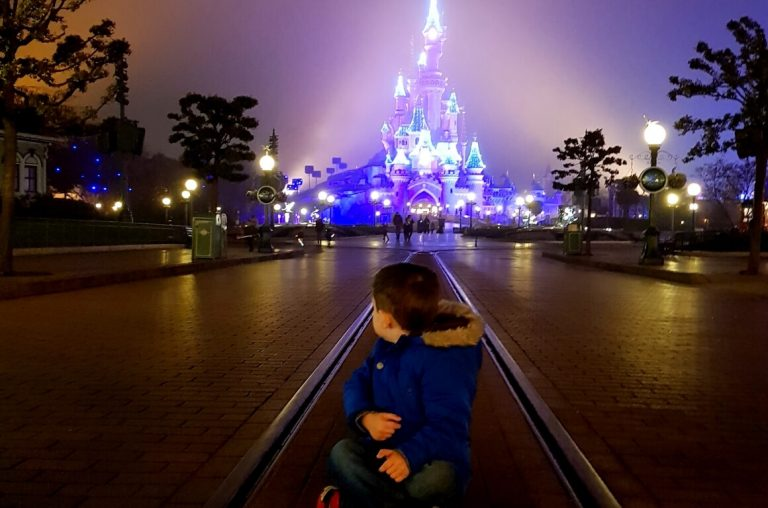 A little boy in a blue coat sitting on the ground with the Disneyland Paris castle in the background