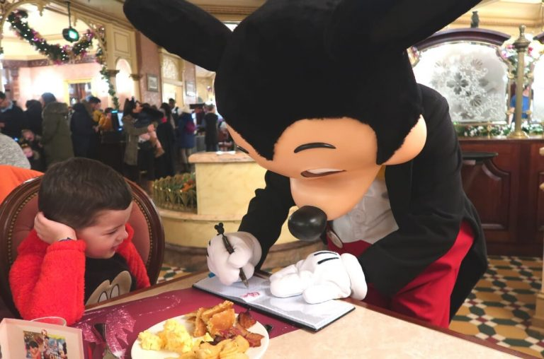Mickey Mouse signing an autograph book for a little boy at Disneyland Paris