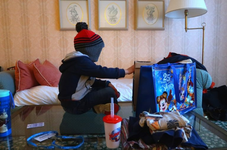 A little boy in a red and grey hat sitting on a table in front of a Disney store bag