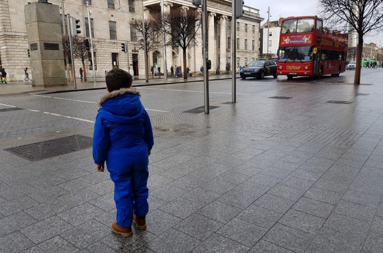 A picture of a boy dresses in a blue rainsuit looking at a red Dublin sightseeing bus on O'Connell Street