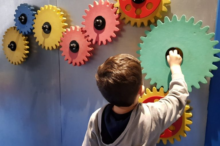 A young boy playing with cog wheels in Imaginosity, the Dublin Children's Museum