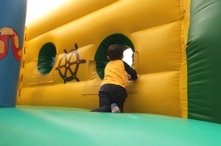 A picture of a young boy in an inflatable play area