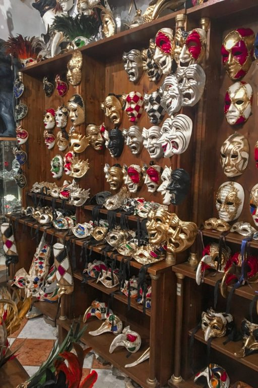 A picture of carnival masks on a wall in a shop in Venice