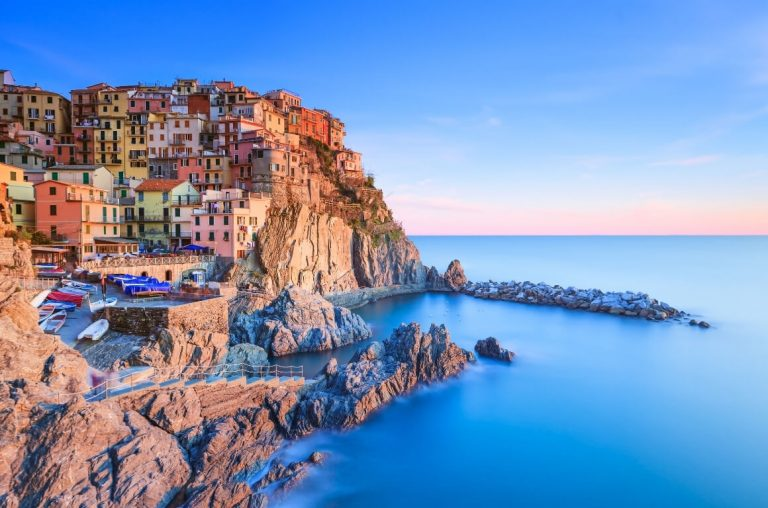 A picture of the Cinque Terre coastline with colourful buildings on the left and the sea on the right