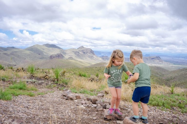 A picture of two kids on a rocky outcrop with the green hills of Big Bend National Park behind them