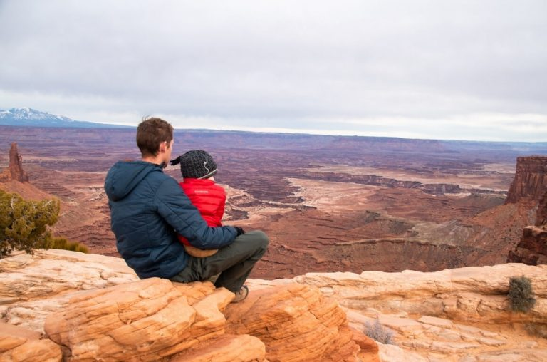 A picture of a Dad and son, sitting on a rock, looking out over the Canyonlands National Park landscape