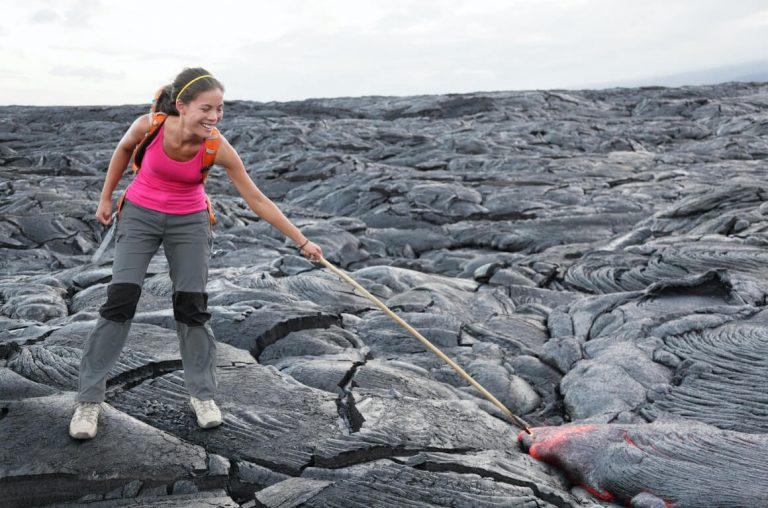 A picture of a woman with a stick poking lava in the Hawaii Volcanoes National Park