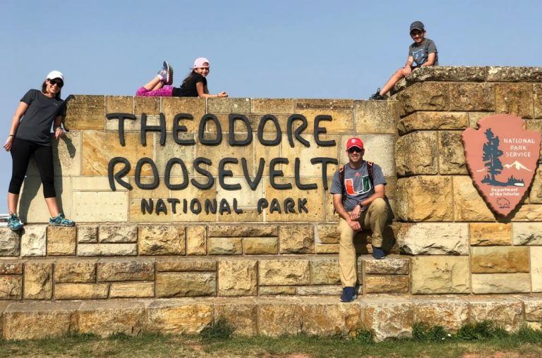 A family of four on the Theodore Roosevelt National Park sign