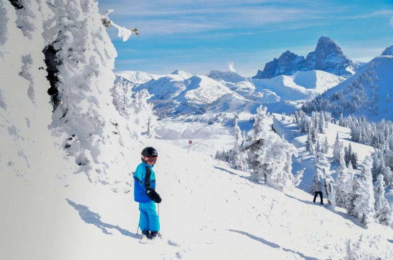 A young boy in blue ski wear on skis in a snowy landscape in Targhee overlooking the Tetons National Park