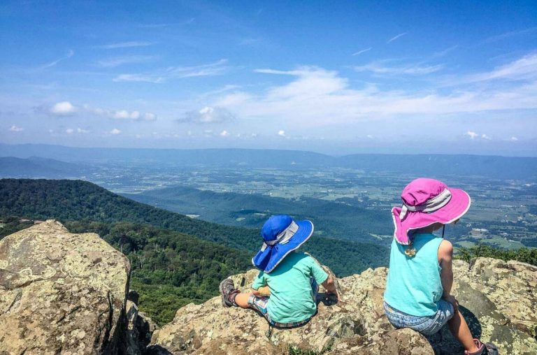 A picture of two kids sitting on a rock looking over a valley in the Shenandoah National Park