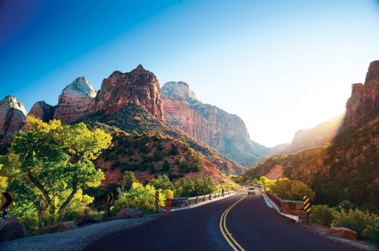 a picture of a road going through Zion National Park with mountains on both sides